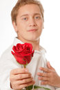 Young man with a flower in her hand isolated on white background Royalty Free Stock Photo