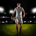Young man football player walks on grass field with ball in hand Royalty Free Stock Photo