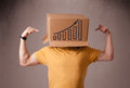 Young man gesturing with a cardboard box on his head with diagra standing and diagram Stock Image