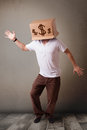 Young man gesturing with a cardboard box on his head with dollar standing and signs Royalty Free Stock Photography