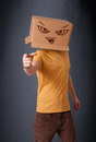 Young man gesturing with a cardboard box on his head with evil f standing and face Royalty Free Stock Photography