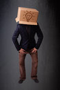 Young man gesturing with a cardboard box on his head with light standing and bulb Stock Photography