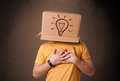 Young man gesturing with a cardboard box on his head with light standing and bulb Royalty Free Stock Image