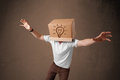 Young man gesturing with a cardboard box on his head with light standing and bulb Royalty Free Stock Photos