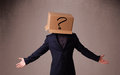 Young man gesturing with a cardboard box on his head with questi standing and question mark Stock Images