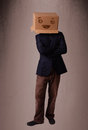 Young man gesturing with a cardboard box on his head with smiley standing and face Stock Image