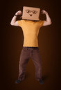 Young man gesturing with a cardboard box on his head with smiley standing and face Stock Photography