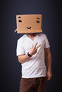 Young man gesturing with a cardboard box on his head with smiley standing and face Royalty Free Stock Image