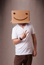 Young man gesturing with a cardboard box on his head with smiley Royalty Free Stock Photo