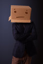 Young man gesturing with a cardboard box on his head with straig standing and straight face Stock Photos
