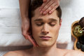 Young man getting spa treatment facial massage at beauty saloon Stock Photography