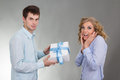 Young man with gift and surprised woman Royalty Free Stock Images