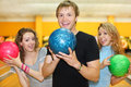 Young man and girls hold balls in bowling club Stock Photos