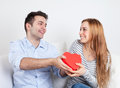 Young man giving a gift to his girlfriend men for valentines day birthday or christmas Royalty Free Stock Images