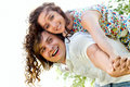 Young man giving piggyback to happy woman Royalty Free Stock Image