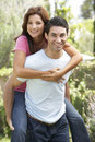 Young Man Giving Woman Piggyback Outdoors Royalty Free Stock Photo