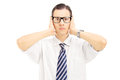 Young man with glasses covering his ears with hands isolated on white background Royalty Free Stock Photo