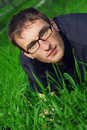 Young man in glasses is liyng green grass Stock Image