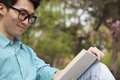 Young man with glasses smiling and enjoying his book, outdoors in a park Royalty Free Stock Photo