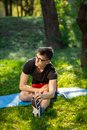 stock image of  Young man in glasses training yoga outdoors. Sporty guy makes relaxing exercise on a blue yoga mat, in park. Copy space