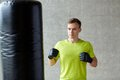 Young man in gloves boxing with punching bag sport box and people concept gym Royalty Free Stock Photo