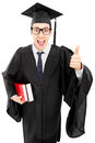 Young man in gown holding books and giving thumb up Royalty Free Stock Images