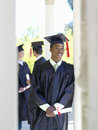 Young man graduating in cap and gown holding diploma men Royalty Free Stock Image