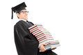 Young man in graduation gown carrying bunch of books isolated on white background Royalty Free Stock Images