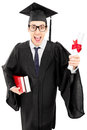 Young man in graduation gown holding books and a diploma Royalty Free Stock Photo