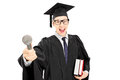 Young man in graduation gown holding a microphone and books Stock Photo