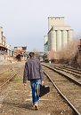 Young man with guitar case in hand going away by rails. Rear view Royalty Free Stock Photo