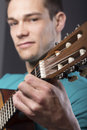 Young man with guitar close up of over gray background Royalty Free Stock Image
