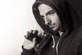 Young man with a gun black and white image of caucasian male in hoodie holding Stock Photos