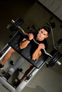 Young man in the gym exercising biceps with barbell performing curls a Stock Photo