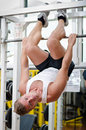 Young man in gym hanging upside down to exercise abs working out exercising by Royalty Free Stock Photo