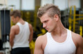 Young man in gym resting and looking down to a side handsome wearing tanktop Royalty Free Stock Images