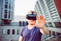 Young man with hand raised in front of him in virtual reality glasses headset standing against modern building background outdoors