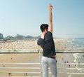 Young man with hand raised pointing up beach in background portrait of a Stock Images