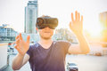 Young man with hands raised in front of him enjoying virtual reality glasses headset on the background of sunset city landscape. T