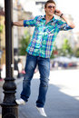 Young man hanging on lamp post Royalty Free Stock Image