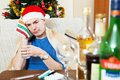 Young man with hangover in santa hat sich sitting at the table glass of water and medication Royalty Free Stock Image