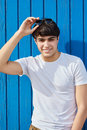 Young man happy man holding sunglasses against blue wooden wall Royalty Free Stock Photo