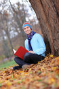 Young man with hat and scarf reading a book Royalty Free Stock Photos