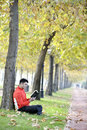 Young man with hat and scarf reading a book outdoors Stock Image