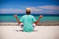 Young man in hat sitting in the lotus position on white sand beach Royalty Free Stock Photo