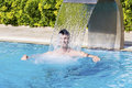 Young man having fun with the water in the swimming pool Royalty Free Stock Photo