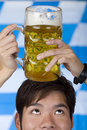 Young man having Oktoberfest beer stein on head Stock Images