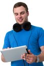 Young man with headphones working on a tablet pc Royalty Free Stock Images