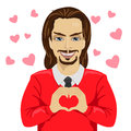 Young man heartthrob making heart shape with his hands on saint valentine day