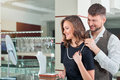 Young man helping his girlfriend with fitting necklace at the je Royalty Free Stock Photo
